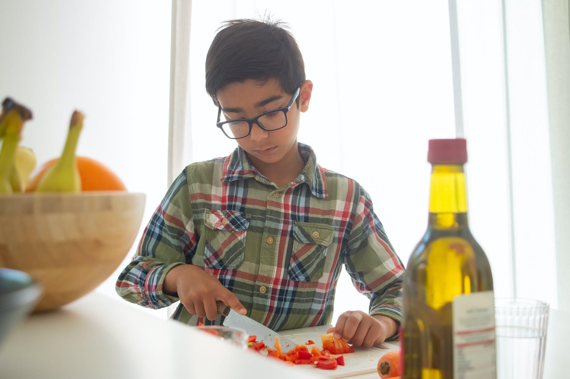 boy slicing tomatoes