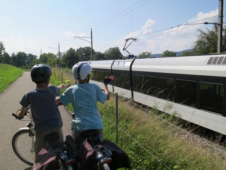 Boy cyclists wave at Swiss Train Arbon to Stein am Rhein