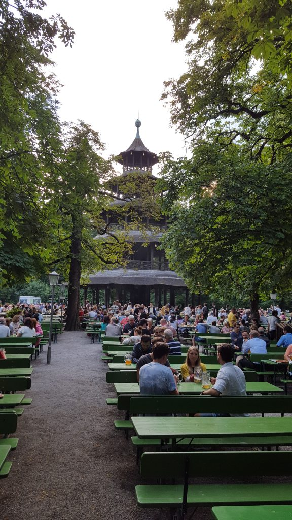 Pagoda and people drinking on a summer evening at English Garten Munich Beer Gardens