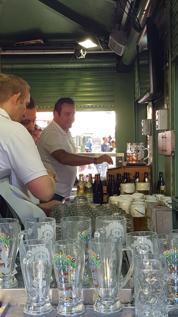 Men serving beer at Viktualien Markt Beer Garden Munich