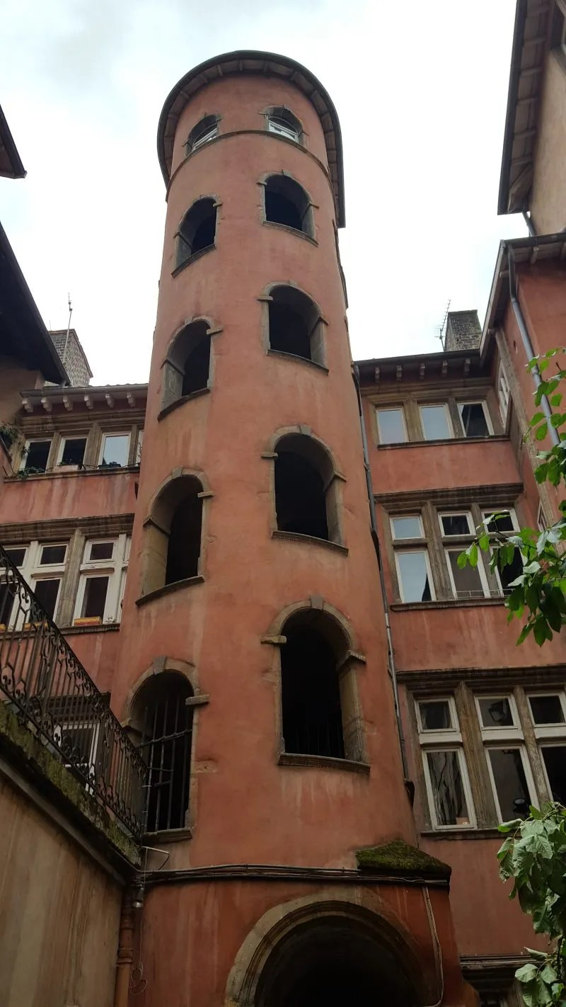 Round red tower with windows housing a spiral staircase in Traboule courtyard Lyon