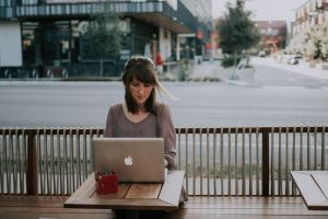 Woman sitting outside cafe with laptop