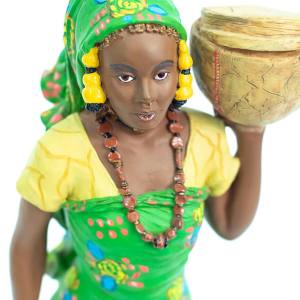 African figurine, Peul woman in green dress holding basket, closeup