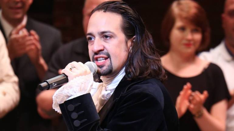 Lin-Manuel dressed as Hamilton, mic in hand