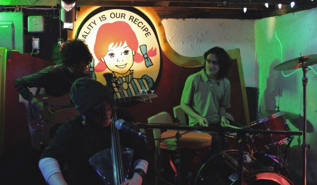 Three musicians play in dim green lighting, with a Wendy's logo on the wall behind them