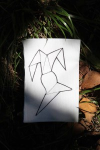 a canvas featuring a geometric image lies against a tuft of grass with dead leaves underneath it