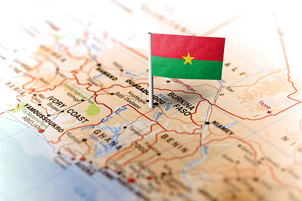 The flag of Burkina Faso pinned on the map. Horizontal orientation. Macro photography.