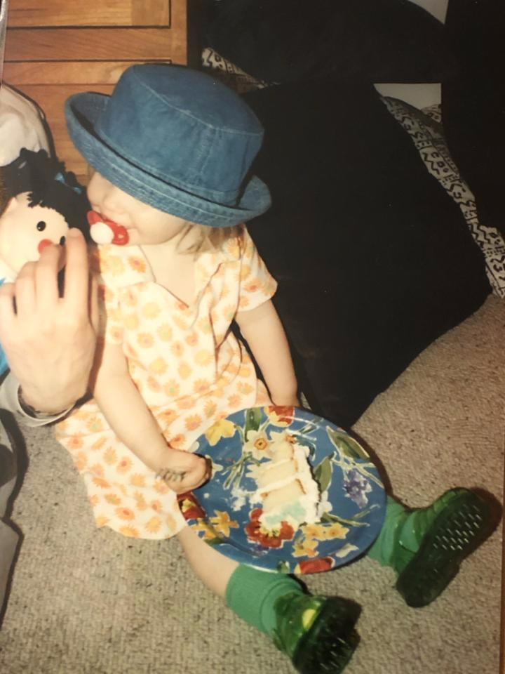 A photograph of Sarah as a two-year-old, with a woobie in her mouth and a slice of cake on a plate in her lap