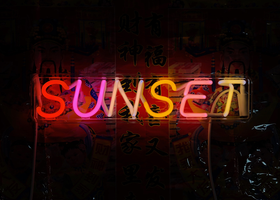 """Sculpture showing the word """"sunset"""" in pink, red, orange, and yellow neon letters"""