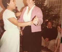 The author's two grandmothers dancing together at a Christmas gathering