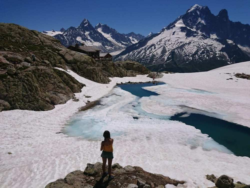 YanYan Yan stands in front of a frozen lake mid hike on the Tour de Mont Blanc (TMB)