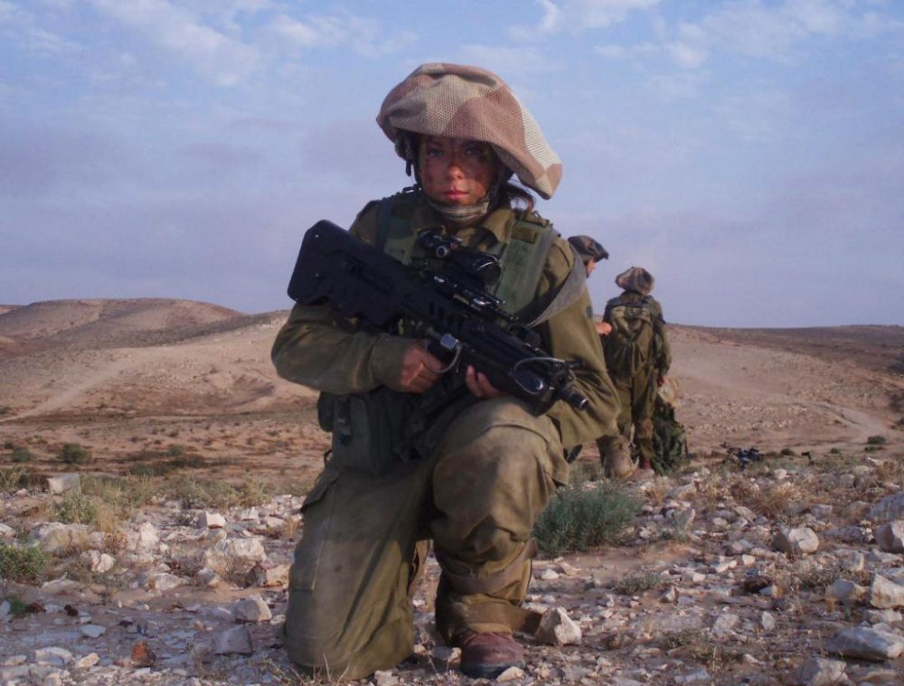 A young female Israel Defense Forces sniper holding an TAVOR/TAR21 rifle