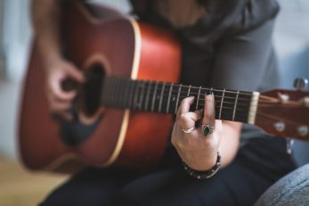 Photo shows image of a woman playing a guitar, an instrument Indigenous artist, Joanna Shenandoah plays.