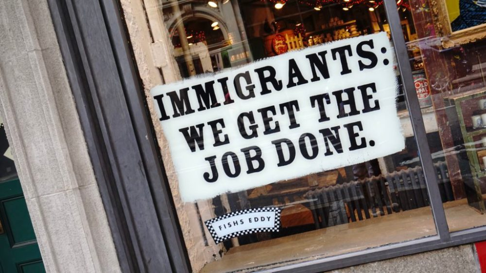"""Immigrants: We get the job done."" sign outside a business."