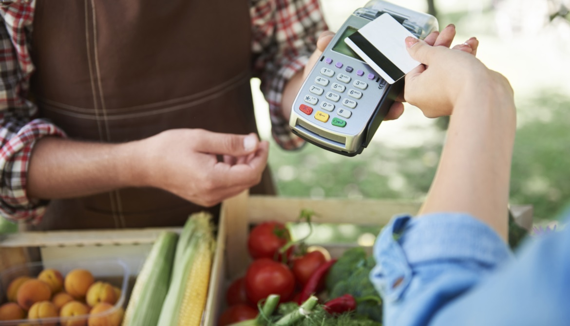 customer using a contactless card to buy produce