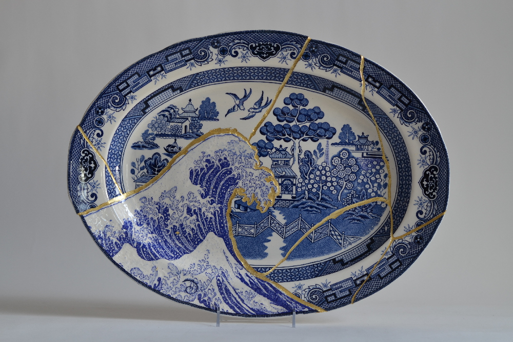 Scott's Cumbrian Blue(s), Fukushima No:5. In-glaze decal collage on broken and re-assembled Willow pattern platter, marked Japan (c.1965) with brass pins, gold leaf, tile cement and epoxy resin. Paul Scott, Cummington MA., 2015.