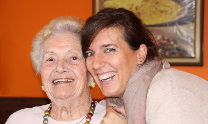 caring for aging parent, older person and younger person smiling