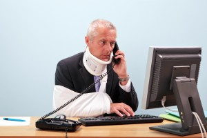 Injured businessman at his desk on the phone