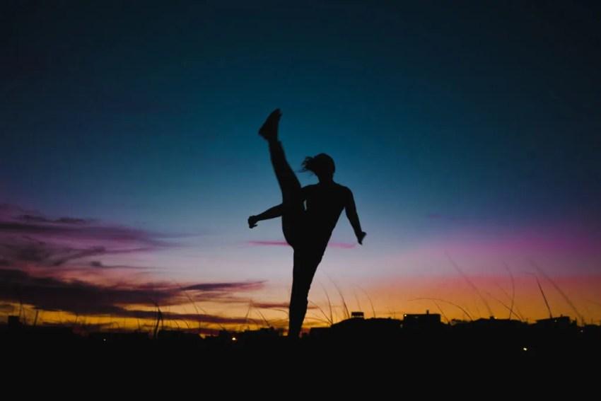 Silhouette of travel girl backpacker doing high-kicks at sunset in Uruguay