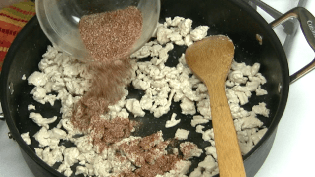adding spice mixture to turkey