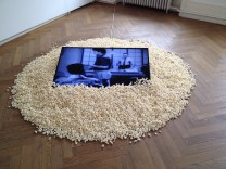 IOCOSE, 2012, First-Viewer Television Installation of First-Viewer Television. A monitor displaying a live streaming of zero-views videos from YouTube, with a side of fresh popcorn.