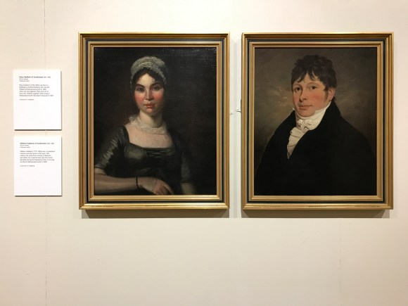 Two portraits hanging side by side in gold gilt frames. One a woman wearing a lace cap and dark blue-black dress, the other a man with short brown hair coming over his forehead, a high collar and black coat.