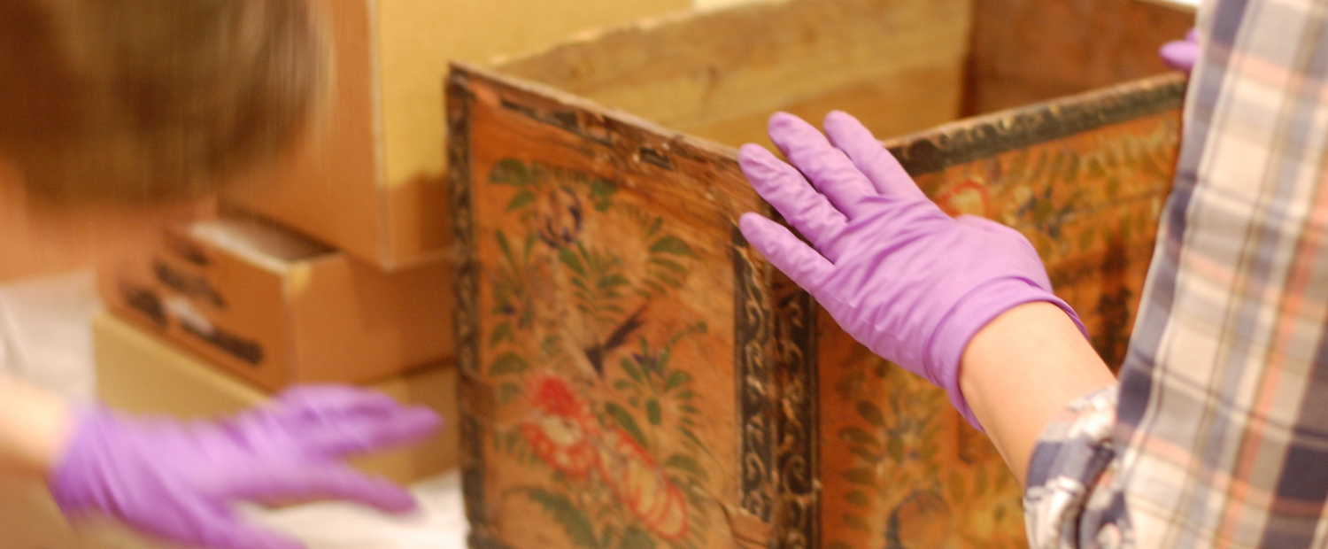 two purple-gloved hands beholding a box with Chinese-style patterns of a pheasant and flowers