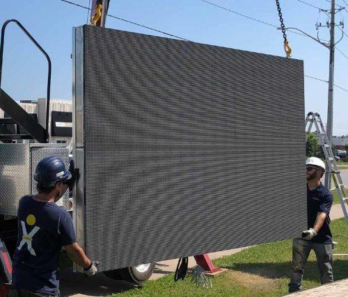 Curbex Employee using a crane to install digital sign