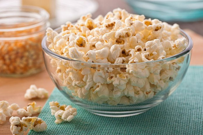 Popcorn is whole grain and has plenty of fiber which keeps you full for a long time as compared to processed crackers.