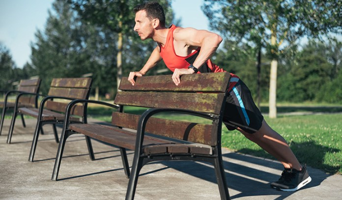 The power pledge exercise makes use of a park bench and targets the shoulders, triceps, chest, and abs.