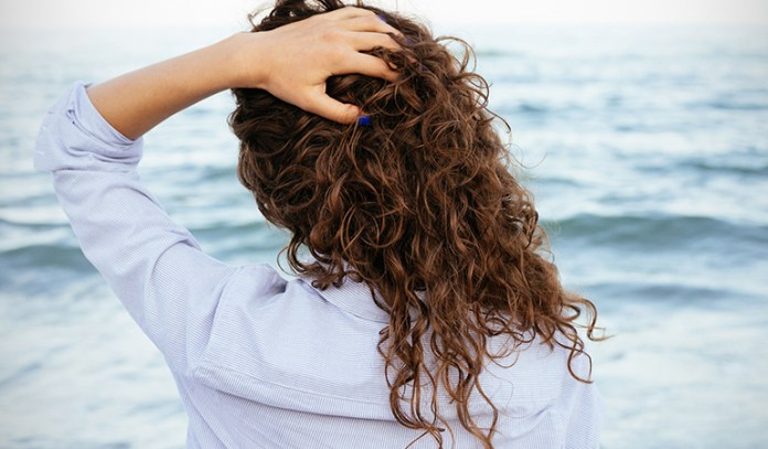 Avoiding friction by using satin-lined scarves and avoiding towel drying will keep your curls frizz-free.