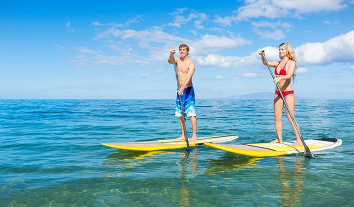 Take to stand-up paddleboarding to improve your balance and engage your core muscles