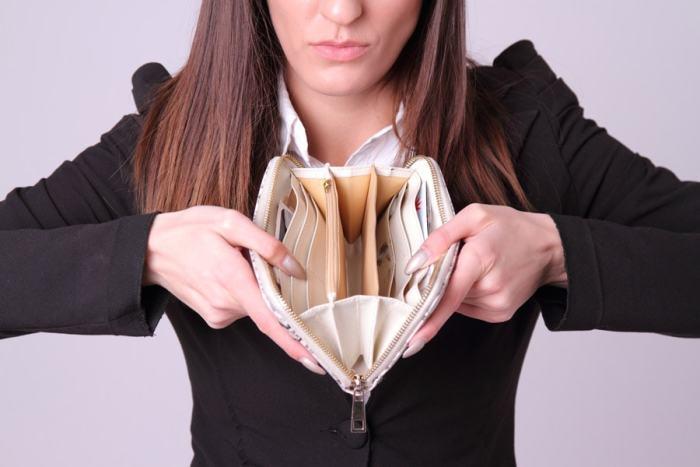空の財布を見せる外国人女性