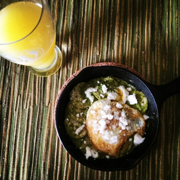 Chilaquiles with Charred Tomatillo and Jalapeno Hot Sauce topped with an egg and queso fresco