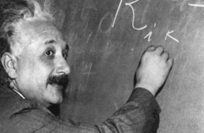 Albert Einstein (1879-1955) who developed the theory of relativity on a blackboard