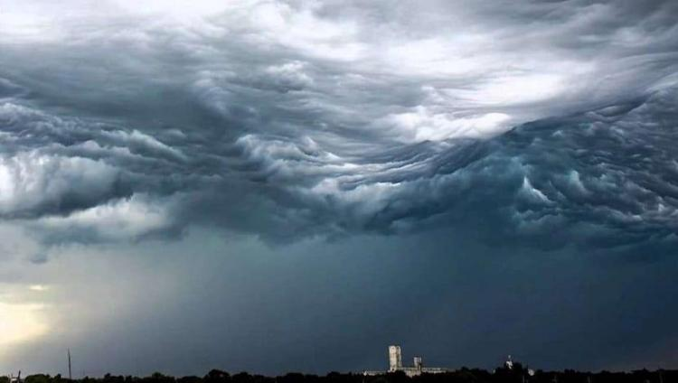A large grey cloud forming over a city skyline.