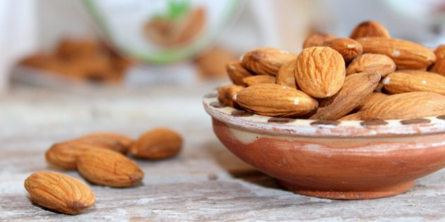 A ceramic brown bowl filled with calcium rich almonds