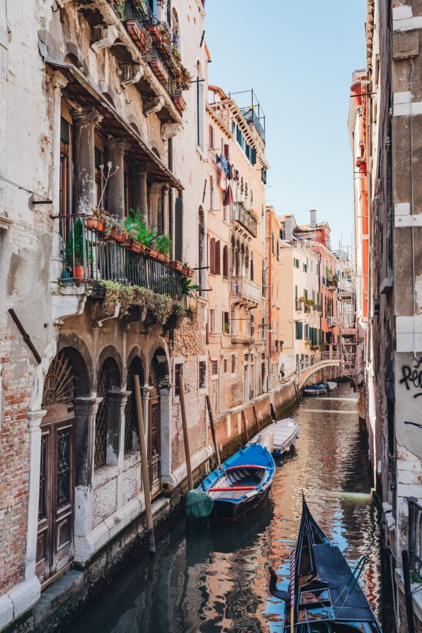 Canal in Venice with boats and flowers sustainable travel Venice