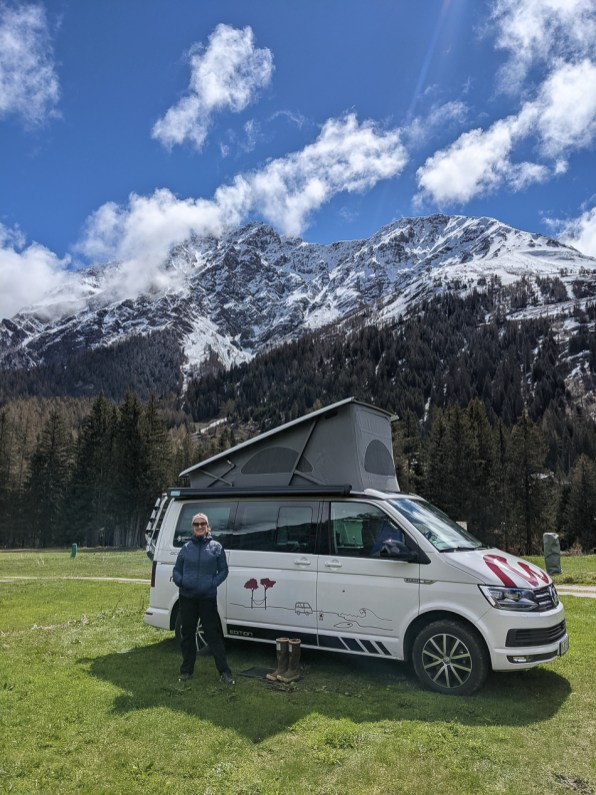 girl standing in front of campervan and mountains in Switzerland