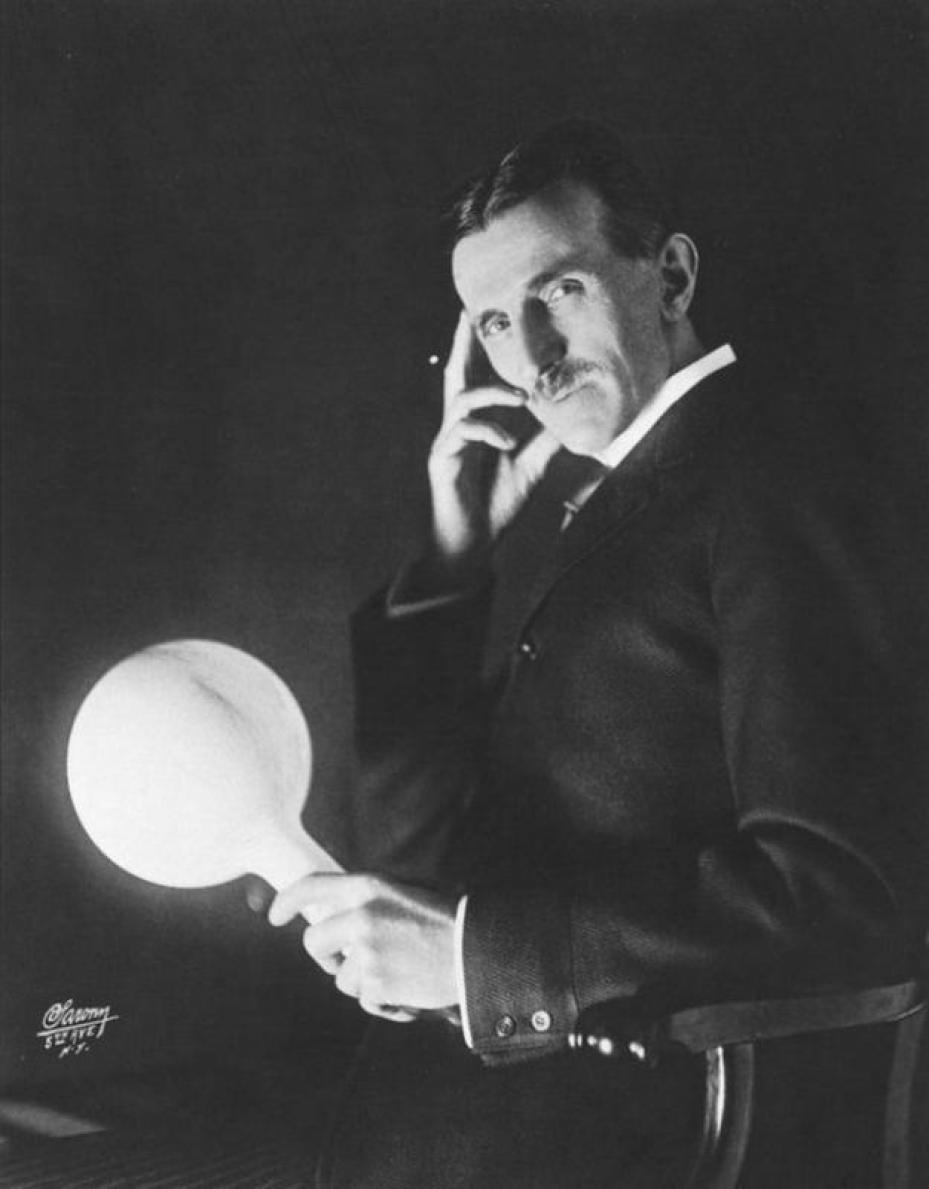 A Photograph of Nikola Tesla holding his gas-filled phosphor-coated wireless light bulb. He developed it in the 1890's.