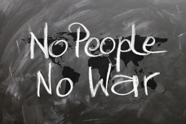 The words 'No people no war' written on a chalk board with a map of the earth