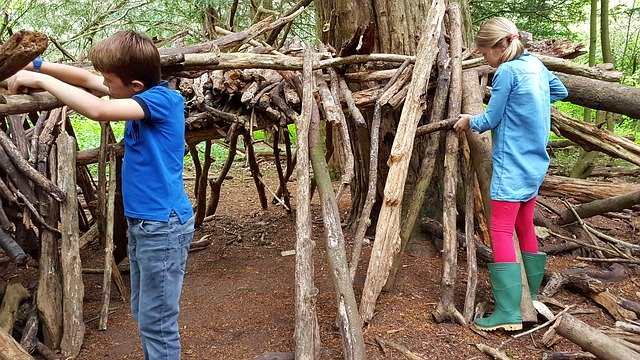 A girl and a boy building a den from large sticks and branches.