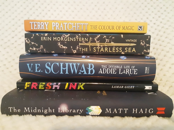 Stack of books including The Colour of Magic, Teh Starless Sea, The Invisible Life of Adie LaRue, Fresh Ink and The Midnight Library