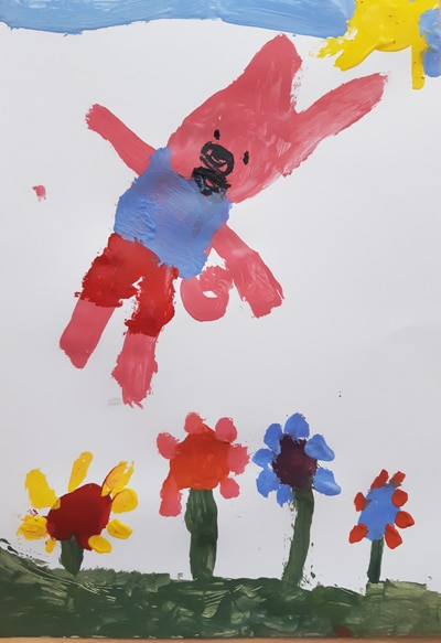child's drawing of a pink pig in blue and red clothing jumping high in a field of flowers