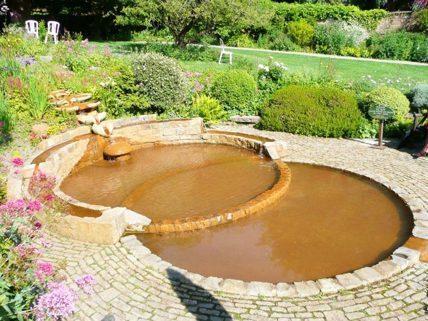 A pond with red water coming from the Chalice Well.
