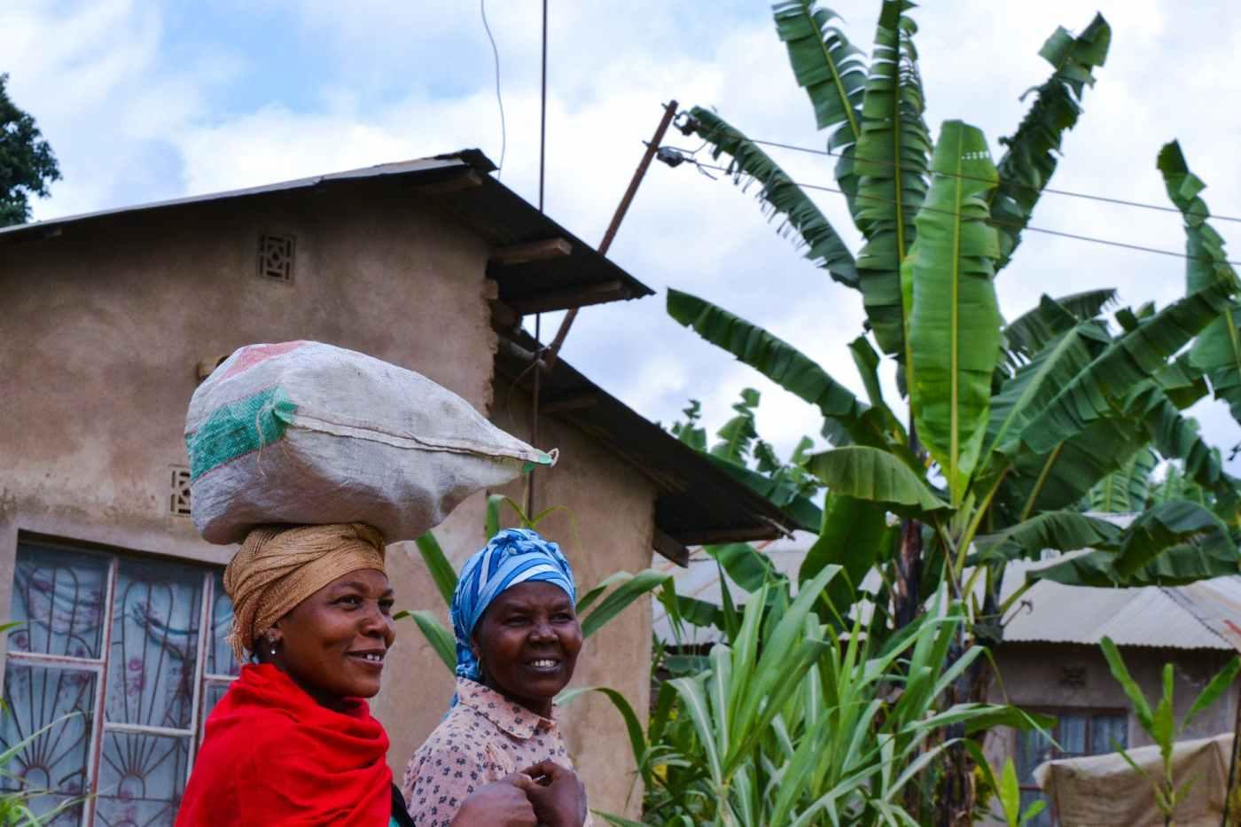two girls walking near the concrete house, learn swahili