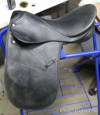 Photo of an older model Courbette Dekunffy Dressage Saddle on ablue saddle rack.