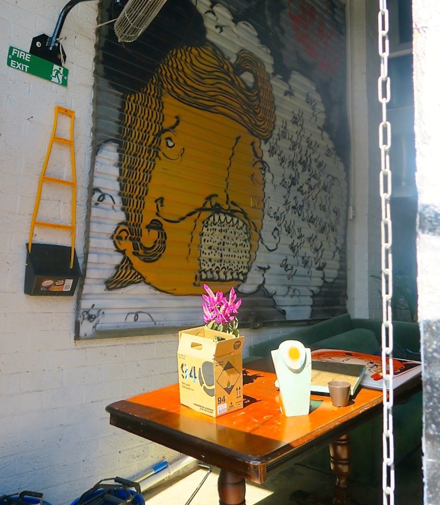 Small office with art on a garage door on the wall |curlytraveller.com