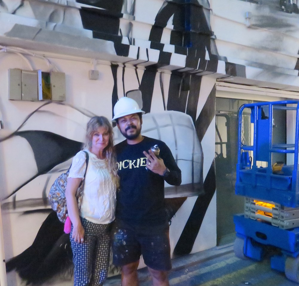 Ceno and a fan in front of a mural in the making |curlytraveller.com