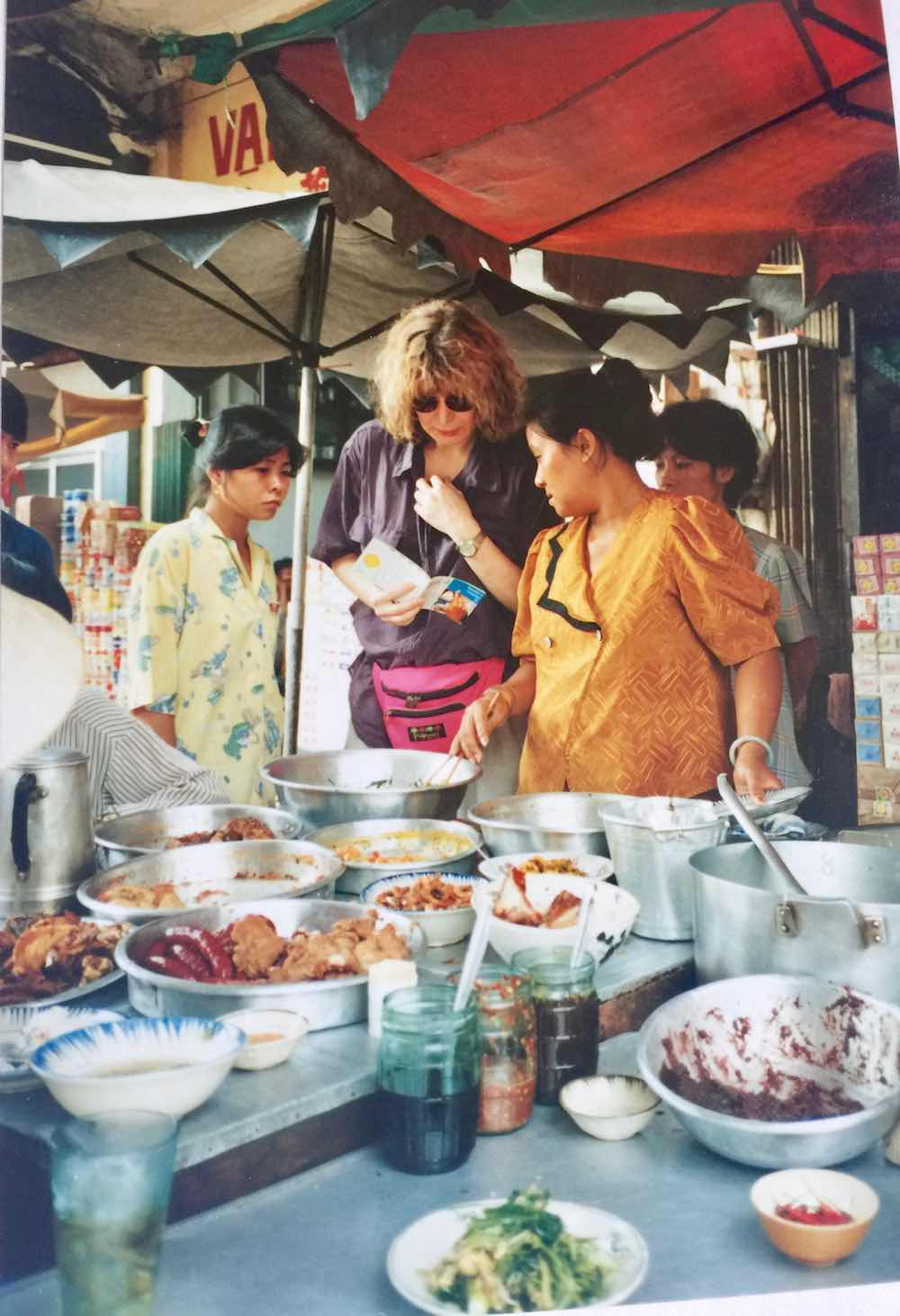 Woman talking with street food vendor in Saigon |curlytraveller.com